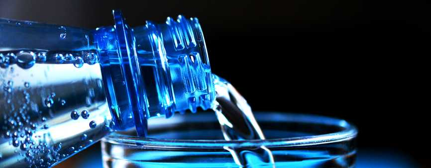 Photo of a bottle of water being poured into a glass.