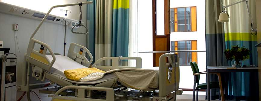 Photo of a bed in a private hospital room.